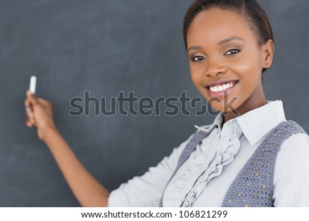 Black teacher looking at camera while holding a chalk in a classroom