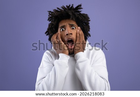 Black teen guy feeling scared, shouting in panic on violet studio background. Terrified African American teenager suffering from phobia, being scared or frightened. Negative human emotions concept Сток-фото ©