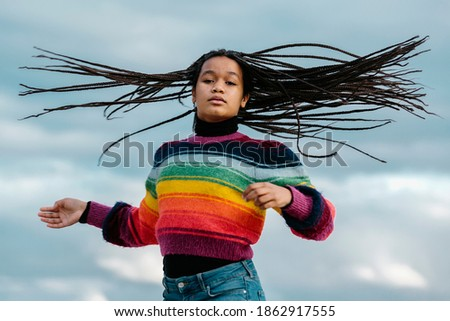 Black teenage girl moving her braids, looking at the camera, in a sky background. Teenagers and black people concept Сток-фото ©