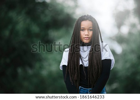 Black teenage girl with braided hair and acne on her face, serious expression, looking at the camera, In a park background with trees. Image with copyspace. Teenagers and black people concept Сток-фото ©