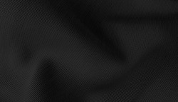 black textile cloth background abstract with soft waves. close up drapery background with softness mood and tone.