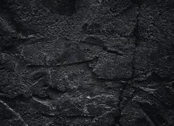 Black texture. Rough structure. Stone black wall. Rock texture. Stone background. Black background. Stone texture. Rock pile background. Rock surface with cracks.