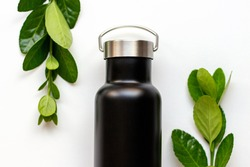 Black thermos with a green leaves on white background, concept reusable