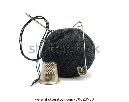 black thread ball, pin, thimble and needle on a white background
