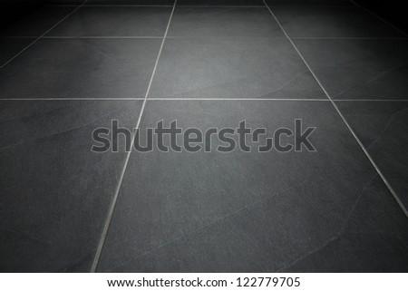 Black tile flooring close up as background
