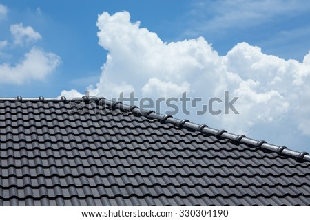 black tile roof of construction house with blue sky and cloud background #330304190