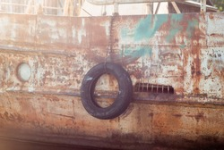 black tire on an old ship at the pier, close-up,