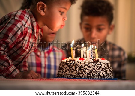 Black toddler blowing candles out. Child blows birthday candles out. Youngest brother\'s birthday. Spending festive time together.