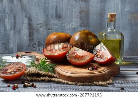 Black tomato kumato in wooden board. Selective focus