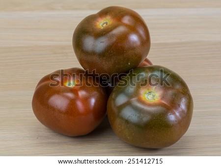 Black tomato - Kumato on the wood background