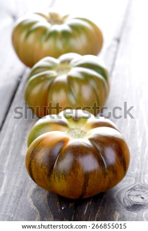 Black tomatoes on wooden table