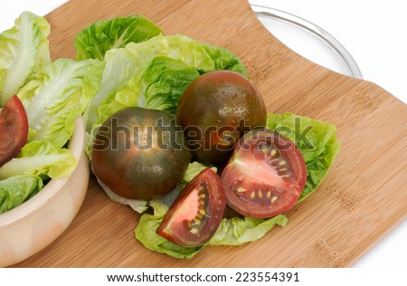 Black tomatoes , whole and cut on a chopping board.