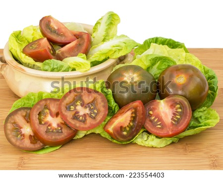 Black tomatoes , whole, cut and sliced on a chopping board