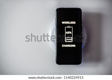 Black touchscreen smartphone wireless charging on induction charger. Wireless charger #1140224915
