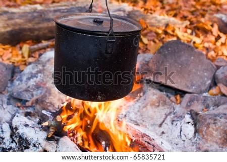 black touristic cauldron in a campfire