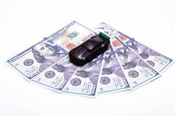 Black toy car on a heap of dollar bills on a white and black background. A sports car with a green spoiler, a wing on dollars in a close-up top and side view. Rear and front car. Selling, buying
