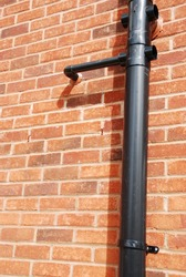 black tube on a brick house wall (used to drain water)