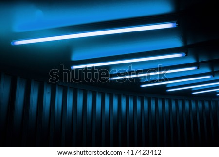 Black tunnel ceiling with cyan blue fluorescent lamps.