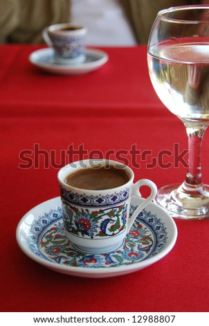 Black turkish coffee and glass water on a red cloth