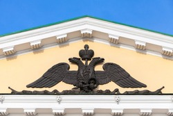 Black Two-headed eagle barelief, Russian coat of arms with a rider on board. Symbol of imperial Russia. Decoration of Saint Petersburg Mining University building