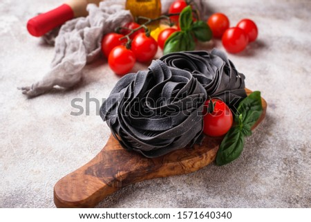 Black uncooked pasta tagliatelle with tomato and basil. Selective focus