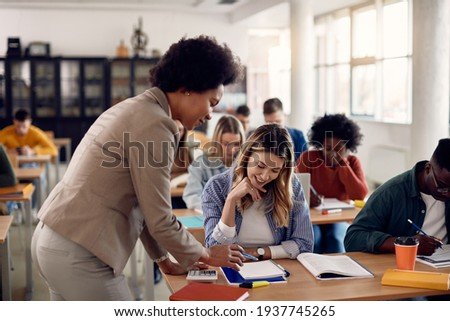Black university teacher assisting her female student with a lecture in the classroom. Focus is on student.