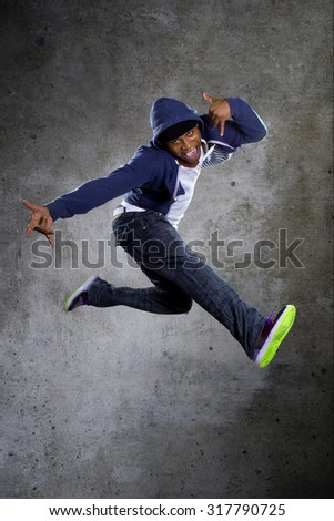Black urban break dancer wearing a blue hoodie and jumping.  The man is energetic and active.