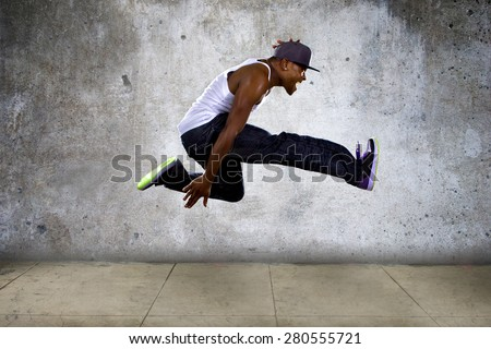 Black urban hip hop dancer jumping high on a concrete background.  The man is doing parkour or leaping. Сток-фото ©