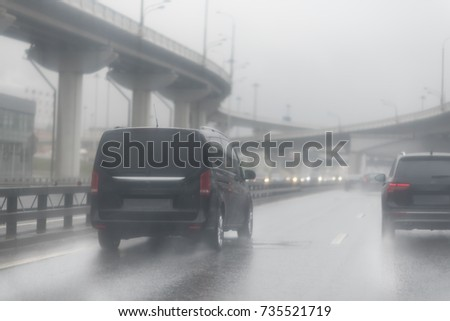 black van and suv are speeding on a wet road. highway junction at the middle of the day. clouds and rain. Seeing as there's heavy shower on a highway and road condition looks quite dangerous. Moscow. #735521719