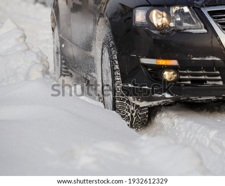 Black vehicle moving through the deep snow skidding, car's wheel spin and spew up pieces of snow it attempts to gain traction on the slippery road. Imagine de stoc ©