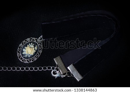 Black velvet choker with rose cameo on a dark background close up #1338144863