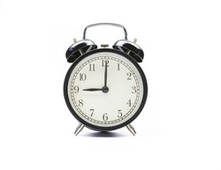 Black vintage alarm clock on a white background shows nine o'clock