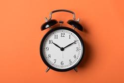 Black vintage alarm clock on orange background. Time concept