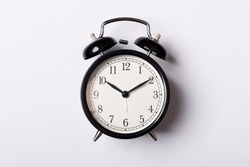 Black vintage alarm clock on white background. Time concept