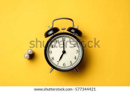 black vintage alarm clock with AA batteries on yellow color background