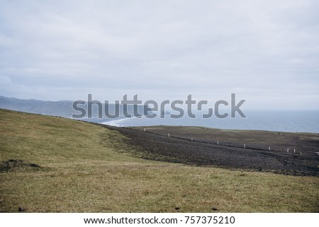 Black volcanic beach at Cape Dyrholaey, South Iceland, with mount Reynisfjall on the background #757375210