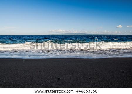 Black volcanic beach near blue sea in Bali island, Indonesia. Island sea shore line with exotic black sand, Bali. Black sea shore sand from Agung volcano, Bali. Volcanic beach in Bali, Indonesia. #446863360