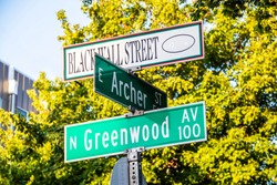 Black Wall Street and N Greenwood Avenue  and Archer street signs - closeup - in Tulsa Oklahoma with bokeh background