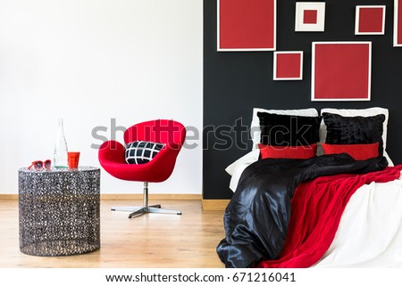 Black wall with artworks in a modern bedroom #671216041