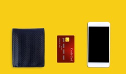 Black wallet, credit card and mobile phone isolated on yellow background.