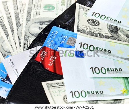 Black wallet with credit cards, euro and dollar banknotes