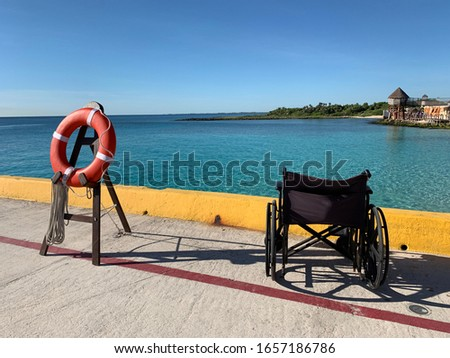 Black wheelchair is on the pier in Costa Maya, Mexico. Cruise ship guest left device. Red life ring  is ready to be used. Blue sea is on a background. View on a thatched roofs .
