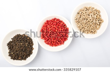 Black, white and pink peppercorn in white bowl over white background #335829107