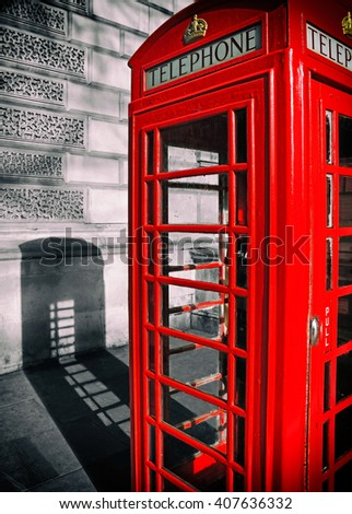 Black & white/ color image of a traditional British red phone box casting a shadow in London, UK. Made to look like film with vignetting applied.