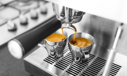 Black & white of espresso being made on home espresso machine. Only the espresso in color.