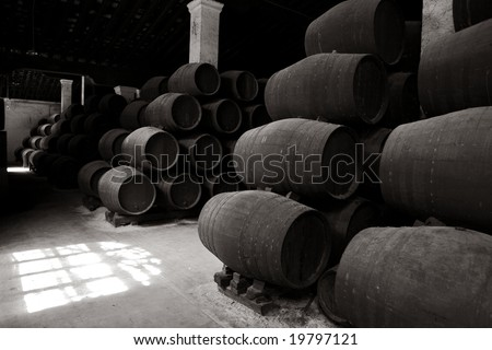 Black & white: old wooden barrels of sherry in bodega of Spanish town of Jerez de la Frontera
