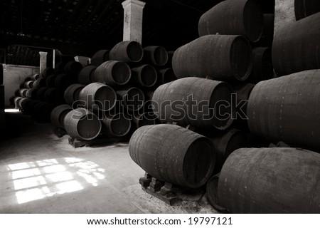 Black & white: old wooden barrels of sherry in bodega of Spanish town of Jerez de la Frontera