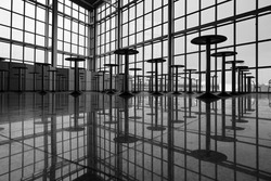Black white photo indoors pattern of chairs with reflection in the floor