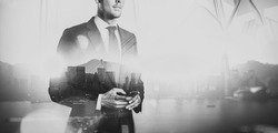 Black white photo of  businessman holding smartphone. Double exposure, city on the background. Wide