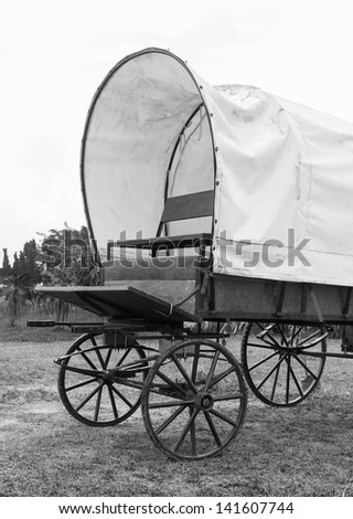 Black & White photo of old wagon wheels Covered wagon  in park